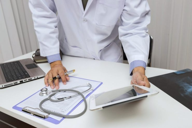 Doctor working with tablet computer at desk. Technology and medical concept.