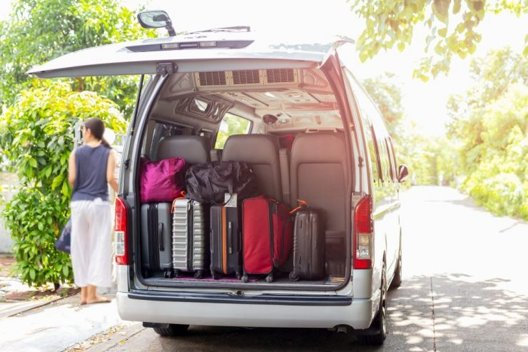 Van with luggage on a sandy with woman in blur backgroung travel