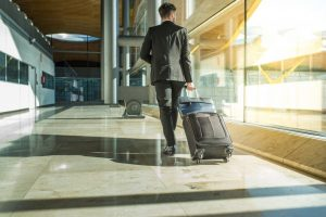 businessman back and lengs walking with luggage at the airport