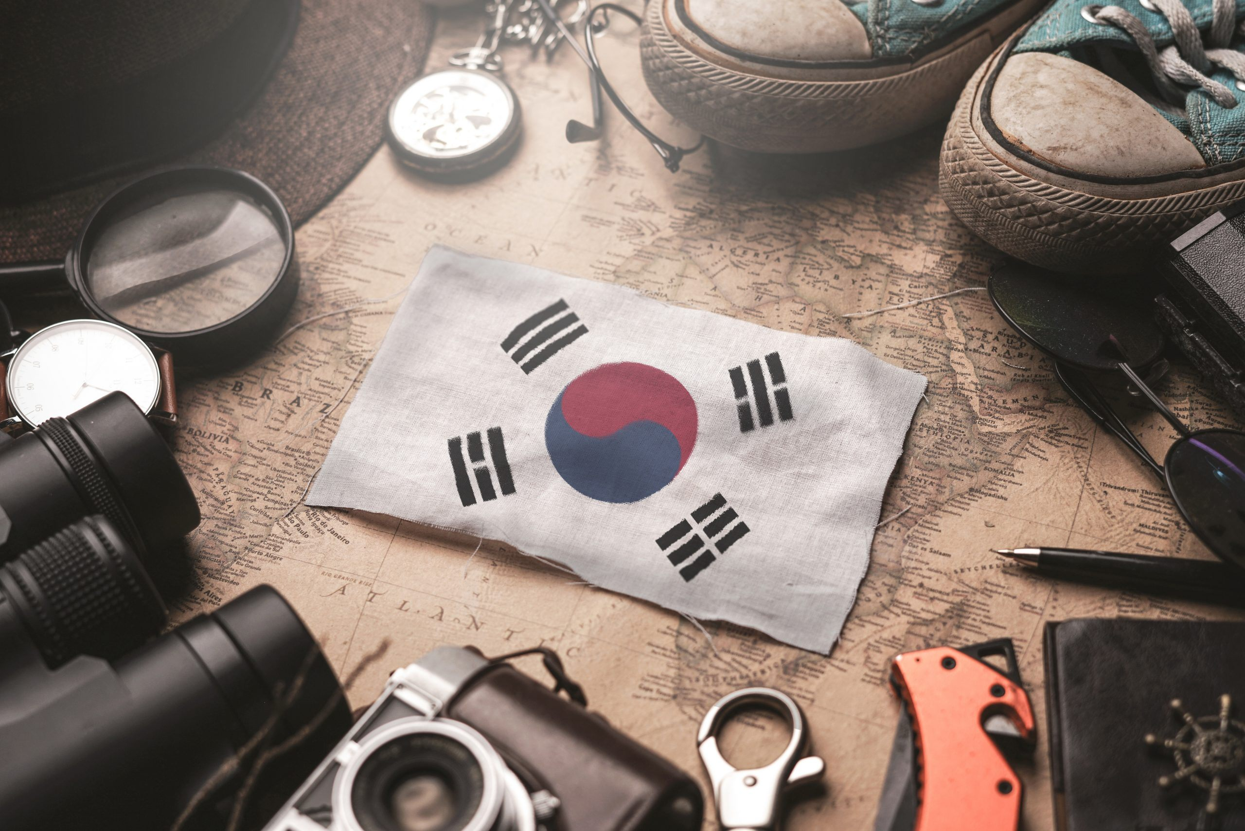 South Korea Flag Between Traveler's Accessories on Old Vintage Map. Tourist Destination Concept.